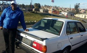 Potwana posing with his car he uses for spinning and for daily use at his home in Mdantsane, NU 11.